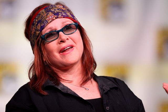 Carrie Fisher wearing a head band and an eye glasses Carrie Fisher net worth